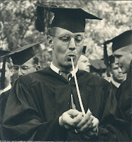 A man in a cap and gown smoking a pipe.