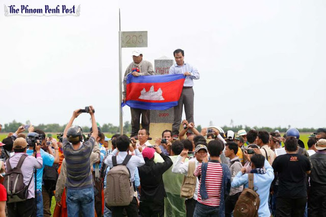 CNRP lawmakers hold a Cambodian flag in front of Border Post 203 in Svay Rieng's Kampong Ro district during a visit to the Cambodia-Vietnam border last year. Vireak Mai