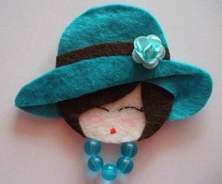 rosto de daminha em feltro com chapéu e flor