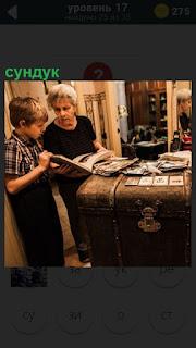 Рядом со старинным сундуком бабушка рассказывает внуку и показывает вещи