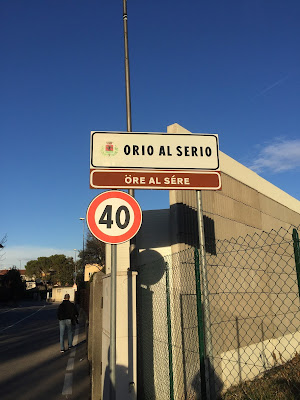 Sign for municipality (comune) of Orio al Serio at the edge of the airport. Underneath is the name of the municipality in the Bergamasco dialect: Öre al Sère).