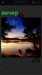 В свете прекрасного заката озеро вечером, в котором отражение солнечных лучей и лодка стоящая на берегу