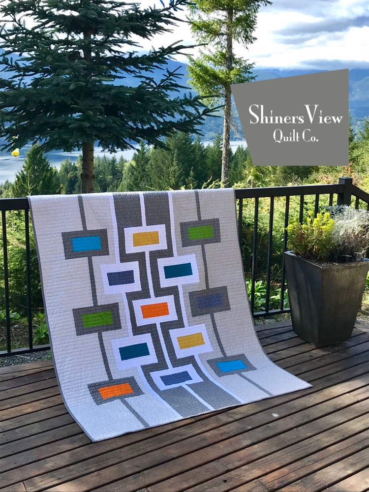 A mid-century modern quilt hanging over a railing with water and mountains in the background
