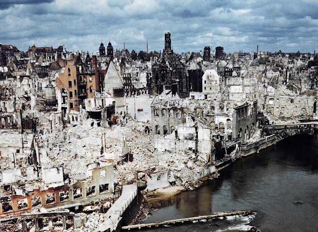 A color photograph of the bombed-out historic city of Nuremberg, Germany in June of 1945, after the end of World War II. Nuremberg had been the host of huge Nazi Party conventions from 1927 to 1938. The last scheduled rally in 1939 was canceled at the last minute due to a scheduling conflict: the German invasion of Poland one day prior to the rally date. The city was also the birthplace of the Nuremberg Laws, a set of draconian antisemitic laws adopted by Nazi Germany. Allied bombings from 1943 until 1945 destroyed more than 90% of the city center, and killed more than 6,000 residents. Nuremberg would soon become famous one last time as the host of the Nuremberg Trials -- a series of military tribunals set up to prosecute the surviving leaders of Nazi Germany. The war crimes these men were charged with included