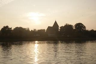 Im Vordergrund befindet sich Wasser. Es ist nebelig, die Sonne geht unter. Auf der anderen Uferseite sieht man Bäume und eine Kirche.