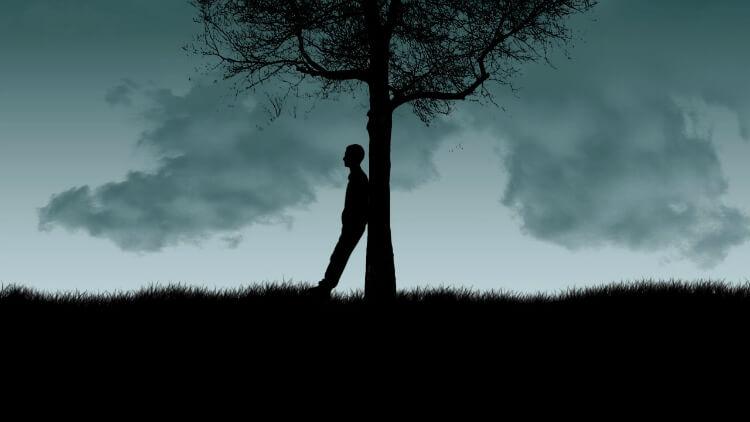 Um homem escorado numa árvore. O cenário é escuro, mas o fundo é um pouco claro com a cor do céu
