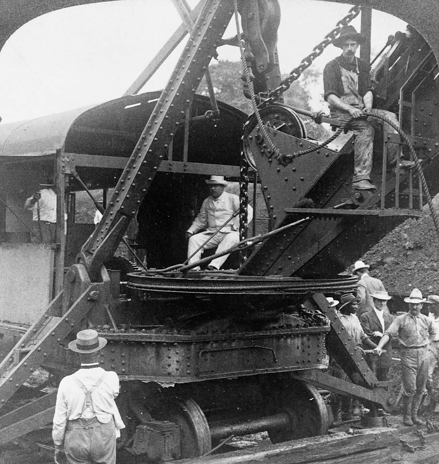 President Theodore Roosevelt sits in the cab of a crane during a visit to the canal construction site. 1906.