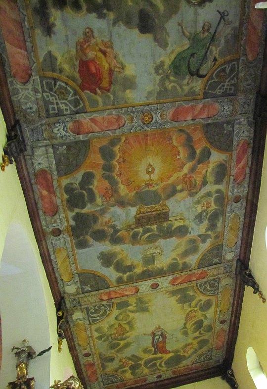 Drewniany strop pokryty polichromiami.