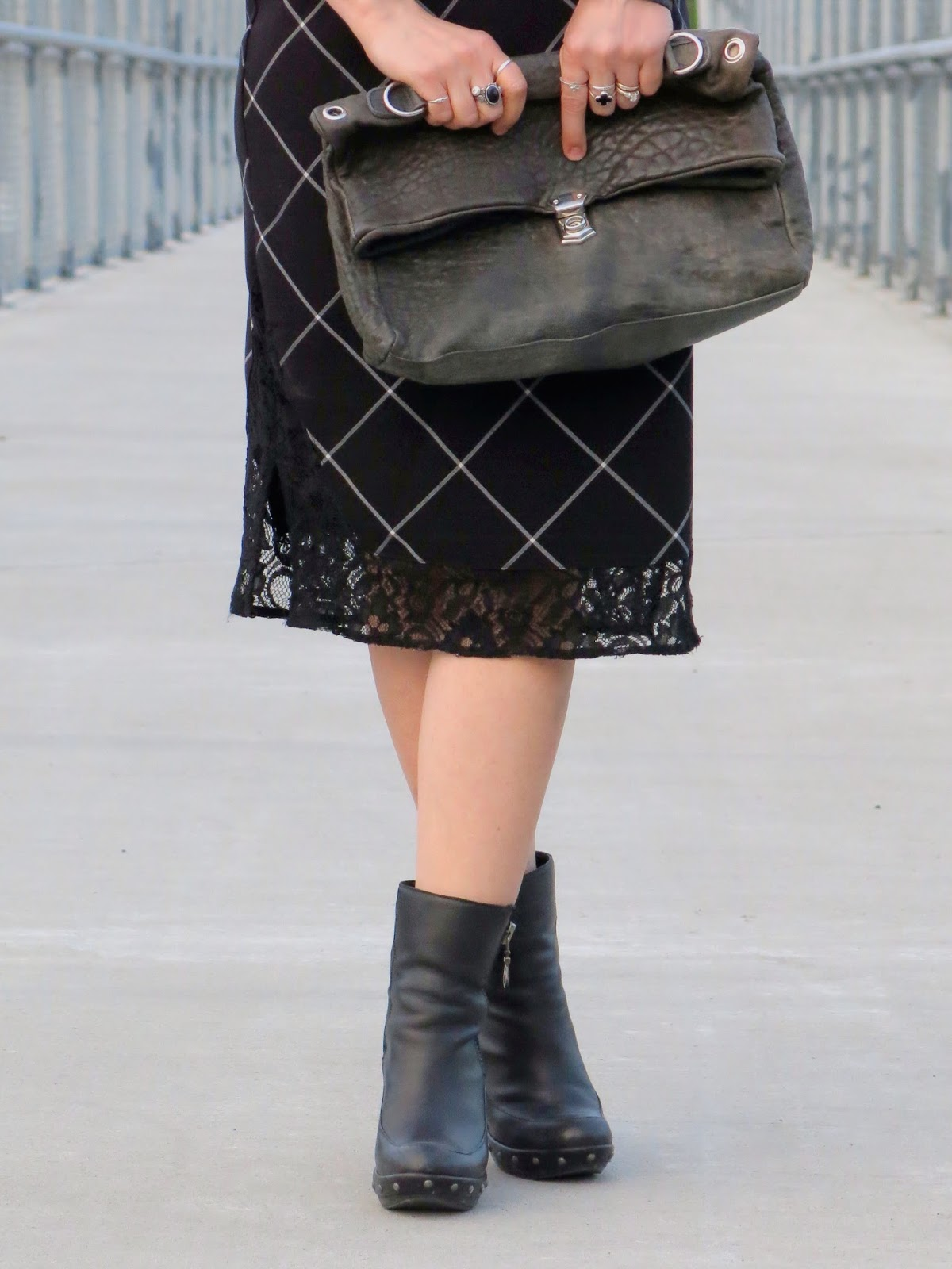 styling a black-and-white plaid slip dress with chunky booties and a satchel