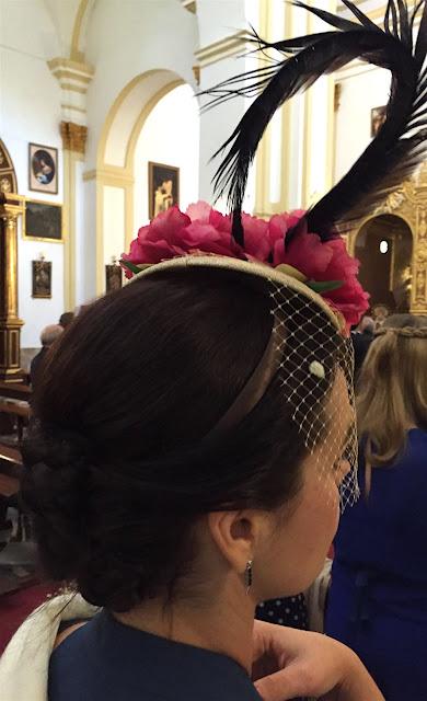Invitada boda con tocado en la iglesia con flores y pluma azul