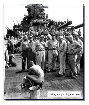 American sailors watch naked emaciated Japanese POW scrubs  deck  American warship