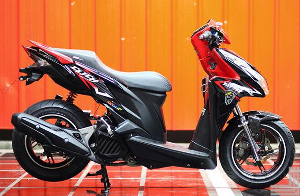 Foto Gambar Modifikasi Honda Vario Techno dengan mengganti ban bagian belakang diubah ukuran besar dari ban depan mengganti jok motor dengan model landai menghilangkan spion pada motor didominasi warna hitam dan merah