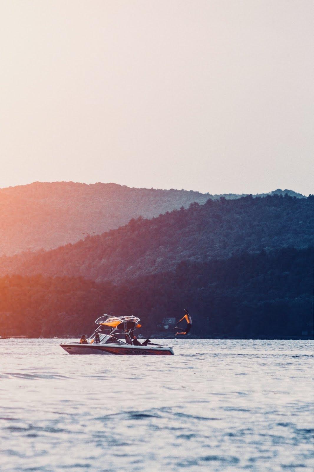 قارب في البحر مع اشعة الشمس الحمراء الرقيقة خلفيات ايفون 6s