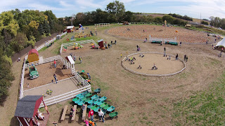 aerial view of Scarecrow Farm pumpkin patch in Lawton, Iowa, showing a big dirt area where pumpkins are placed, plus sevearl play areas surrounded by white fencing. inside the play areas, trikes, and a slide that looks like an old farm truck are visible