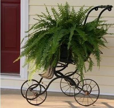 Manfaatkan troli atau kereta bayi yang sudah rusak sebagai vas atau pot bunga hias di depan rumah