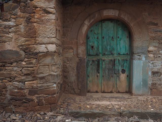 Puerta de madera turquesa en una fachada de piedra rojiza