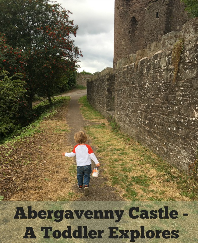 Abergavenny-castle-a-toddler-explores-text-over-image-of-toddler-at-entrance-to-castle