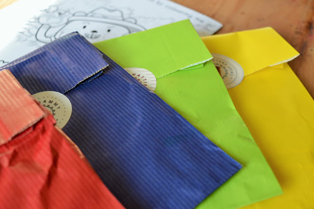 Four sealed paper bags in red, blue, green and yellow.