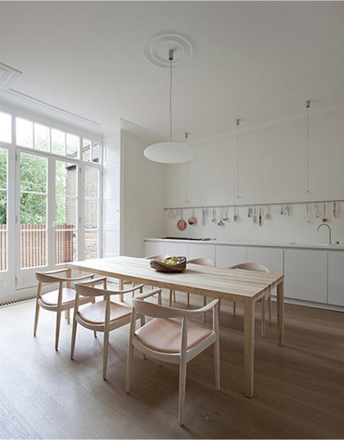 In der Mitte der Küche steht ein Holztisch mit sechs Stühlen. Durch die großen Fenster fällt viel Licht in den Raum.