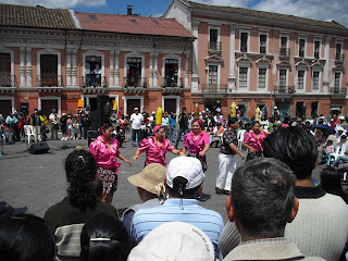 A colourful, local dance watched by an enthusiastic crowd on a sunny day in central Quito, Ecuador