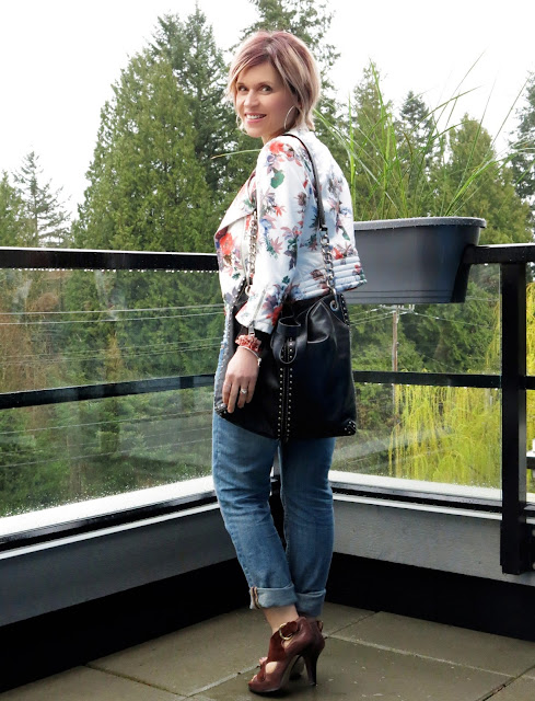 styling a white floral moto jacket over a sheer black floral top, with boyfriend jeans and suede Nine West heels