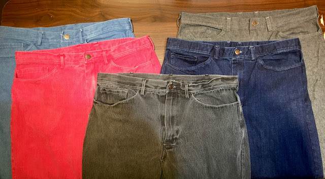 Five pair of jeans, light blue, red, dark gray, dark blue and medium gray.