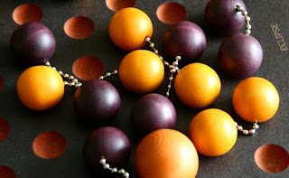 A close up of the pieces on the board in the middle of a game. You can see several vacant holes, but most of them are occupied by the little pairs of wooden balls linked by dog-tag style chains. Some of these pairs are a light orangish-brown colour; the others are a dark purpley-brown. A couple of the pairs are arranged so that their chains cross over the chain of another pair. In the bottom of the picture, one of the light coloured balls is larger than all the others, and is not linked to another.
