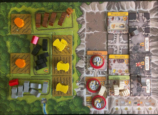 A single player board, with various pieces arranged on it. The board has two halves: the cavern half and the forest half. Each is subdivided into twelve squares. Some of those squares have tiles representing conversion into tunnels, mines, or living areas (in the cavern half) or livestock pens and crop fields (the forest half). There are tokens of various types on these tiles.