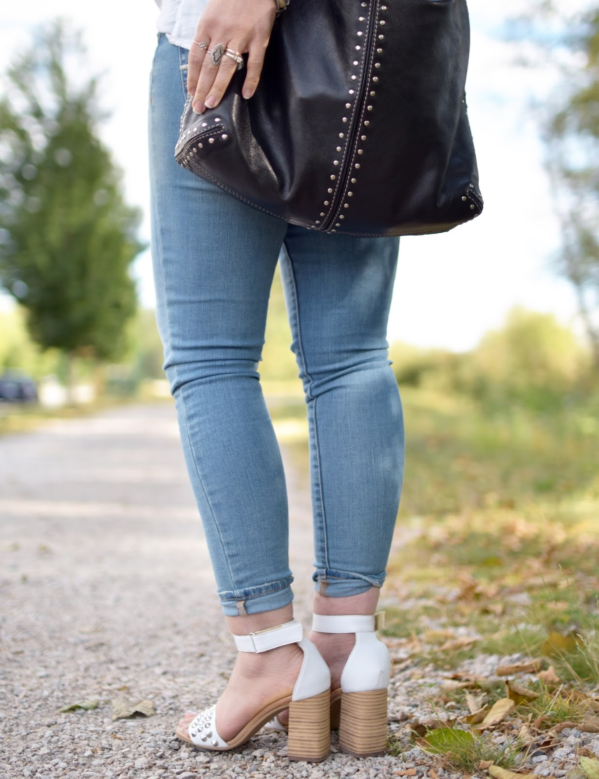 skinny jeans, white block-heeled sandals, studded Michael Kors bag
