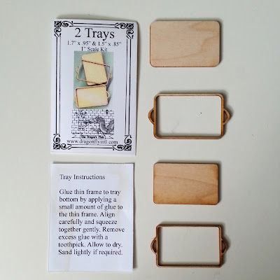 One-twelfth scale miniature tray kit pieces arranged next to the instructions.