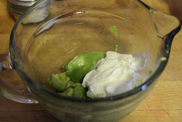 A picture of a mixing bowl with the avocado and sour cream in it.