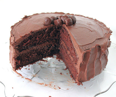A close up photo of a nigella\'s chocolate fudge cake with a big slice removed.