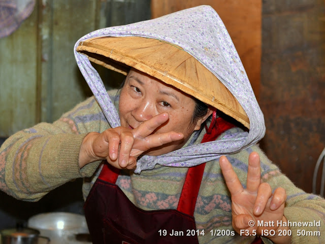 Asian conical hat, conical straw hat, sedge hat, rice hat, paddy hat, Taiwanese market woman with conical hat, portrait, Taiwan, Kaohsiung, V sign