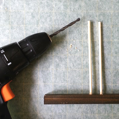 Electric drill laid next to a length of wood with two dowels sticking out of the top of it.