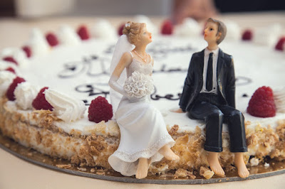 A thin cake with a same-sex couple topper sitting on the edge