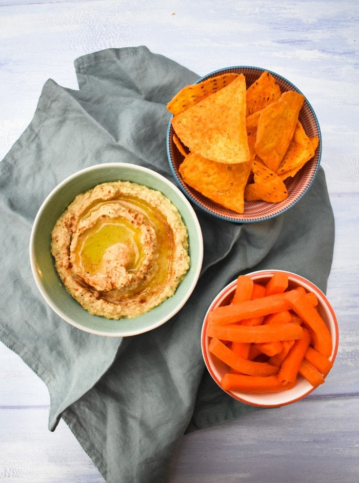 homemade hummus in a bowl beside a bowl of carrot stick and a bowl of cheesy nacho chips