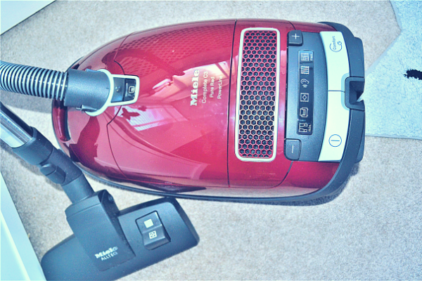 Miele Complete C3 Pure Red Bagged Cylinder Vacuum Cleaner lying down on the floor photographed from above showing the digital display