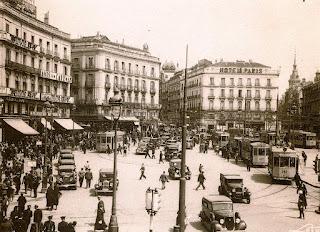 Vista general de la plaza con numerosos viandantes, coches y tranvías de la época