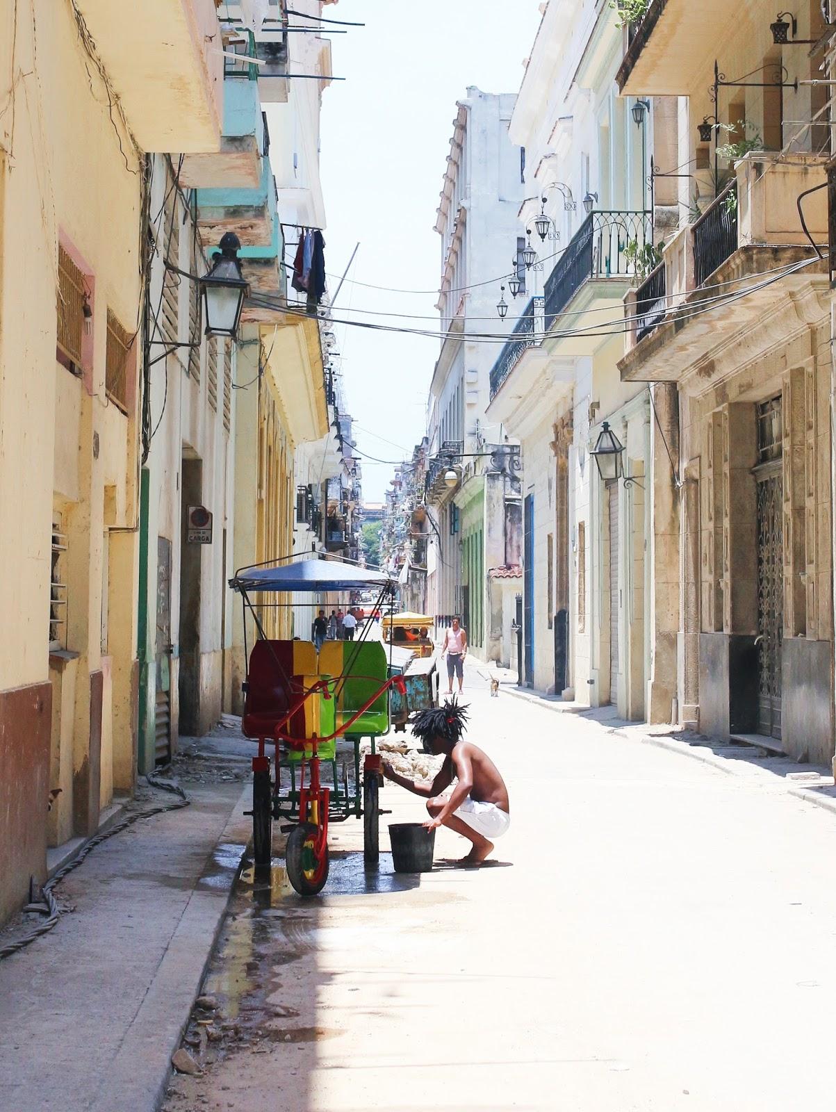 Dans les rues de La Havane - Nettoyage d'un tuk-tuk aux couleurs de la Jamaïque