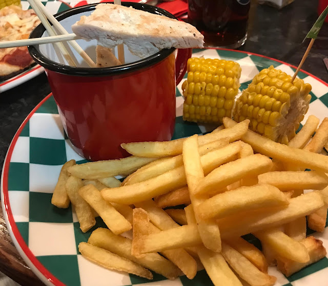 Kid meal of fries, corn on cob and chicken sticks