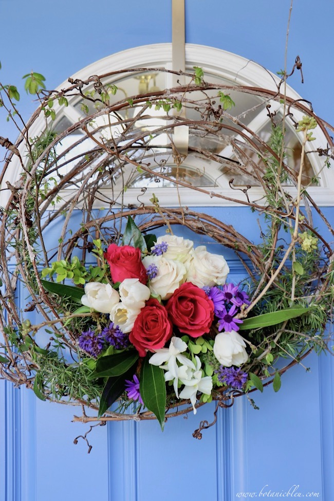 live flowers in a grapevine wreath on a blue front door