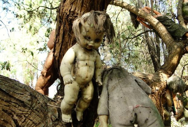 boneka menyeramkan tergantung disebuah pohohn di pulau boneka