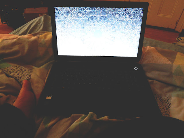 Laptop on top of a bed