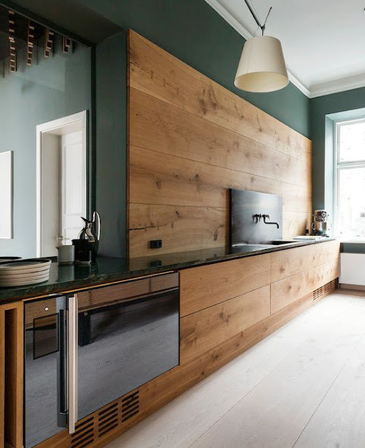 Deep and dark green walls in a rustic kitchen with wood backsplash on Hello Lovely