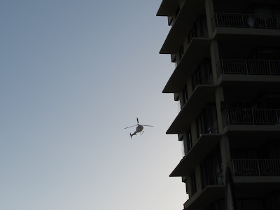 Helicopters hover near building at sunset