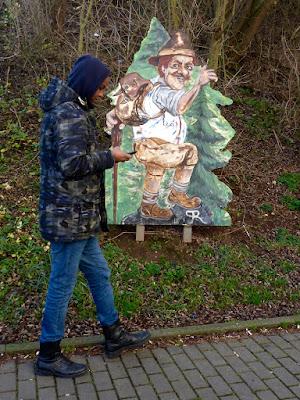 Schreitender dunkelhäutiger Knabe mit Handy vor zünftigem Wandersmann als gezeichnete Abbildung