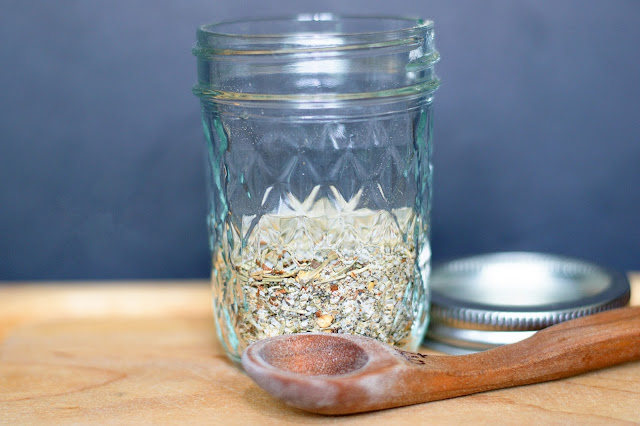 The finished Homemade Montreal Seasoning in a mason jar, with a measuring spoon in front of the jar.