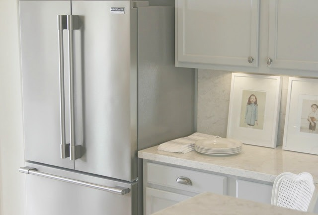 Serene simple chic Nordic French kitchen with stainless refrigerator and Soprano quartz countertop
