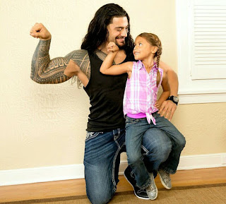 Roman Reigns and daughter flexing biceps