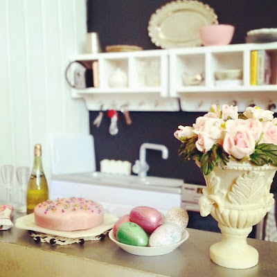 Modern dolls house miniature kitchen in colours of white, grey, black and pink. In the foreground is a vase of roses and an easter afternoon tea laid out.